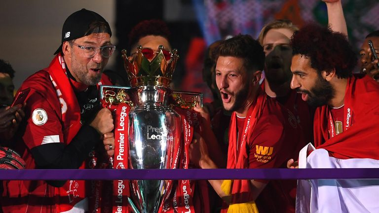 Jurgen Klopp lifts the Premier League trophy with Adam Lallana and Mohamed Salah
