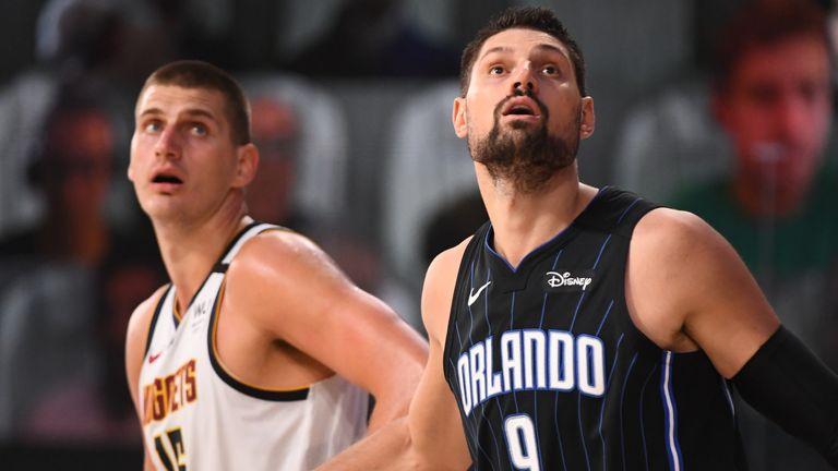 Nikola Jokic and Nikola Vucevic compete for a rebound