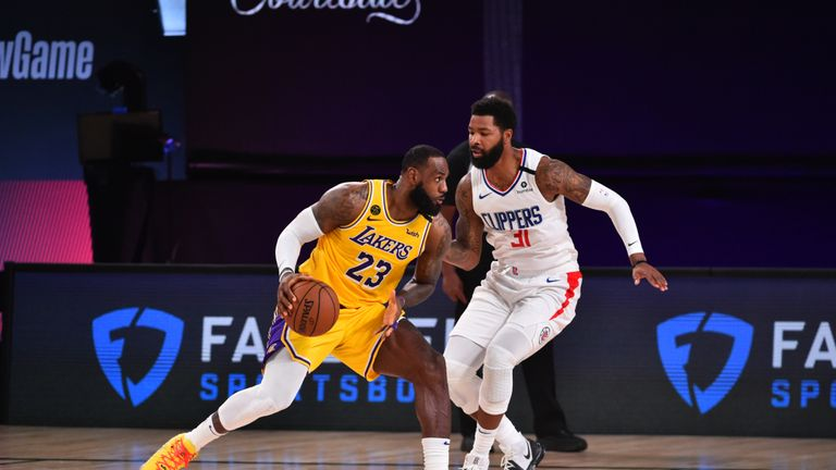 LeBron James #23 of the Los Angeles Lakers handles the ball against Marcus Morris Sr. #31 of the LA Clippers on July 30, 2020 at The Arena at ESPN Wide World Of Sports Complex in Orlando, Florida.