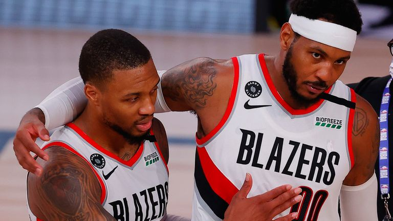 Damian Lillard gets a hug from Blazers team-mate Carmelo Anthony