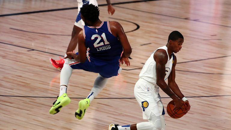 Joel Embiid takes a heavy fall after chasing a wayward pass from team-mate Shake Milton
