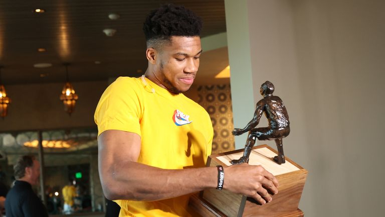 Giannis Antetokounmpo examines his trophy after being named the 2019-20 Defensive Player of the Year