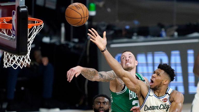 Milwaukee Bucks' Giannis Antetokounmpo heads to the basket as Boston Celtics' Daniel Theis defends