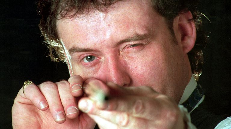 SNOOKER PLAYER JIMMY WHITE LOOKS STRAIGHT DOWN HIS CUE TO CHECK IT DURING A BREAK AT THE WORLD SNOOKER CHAMPIONSHIPS IN SHEFFIELD.