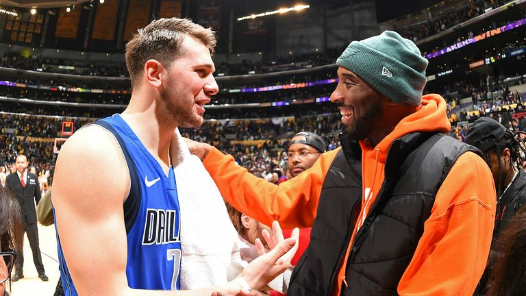 Luka Doncic #77 of the Dallas Mavericks talks to Kobe Bryant during the game against the Los Angeles Lakers