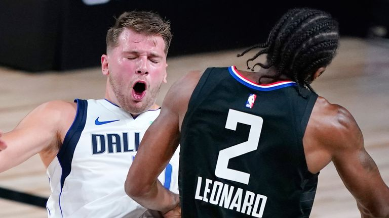 Luka Doncic takes a charge from Kawhi Leonard