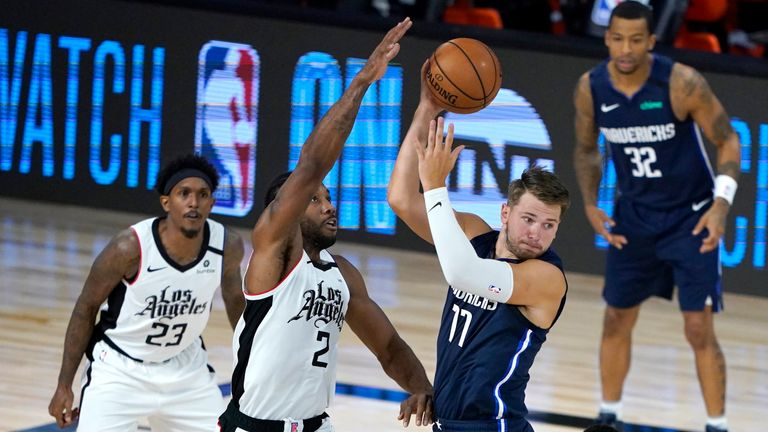 Dallas Mavericks' Luka Doncic looks to pass against the defense of Los Angeles Clippers' Kawhi Leonard
