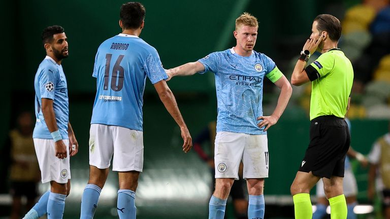 Man City players wait for a VAR check to take place to see if Lyon's second goal will stand