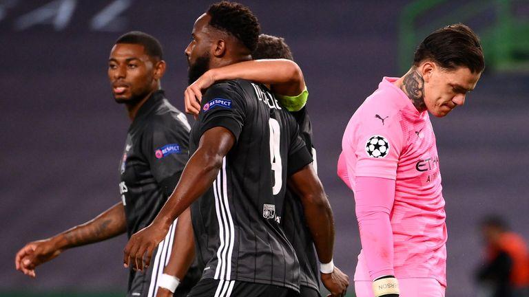Moussa Dembele celebrates scoring for Lyon as Manchester City goalkeeper Ederson looks on