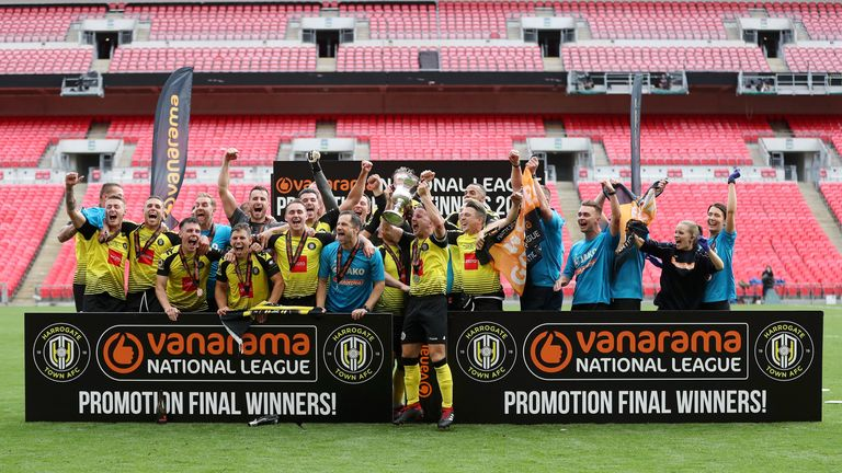 Harrogate Town players and staff celebrate with National League play-off final trophy at Wembley after beating Notts County 3-1
