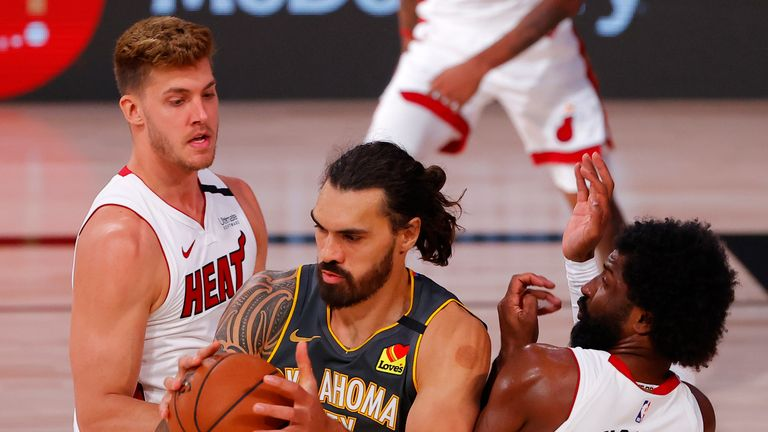 Steven Adams #12 of the Oklahoma City Thunder grabs a rebound against Meyers Leonard #0 and Solomon Hill #44 of the Miami Heat during the third quarter at Visa Athletic Center at ESPN Wide World Of Sports Complex on August 12, 2020 in Lake Buena Vista, Florida.