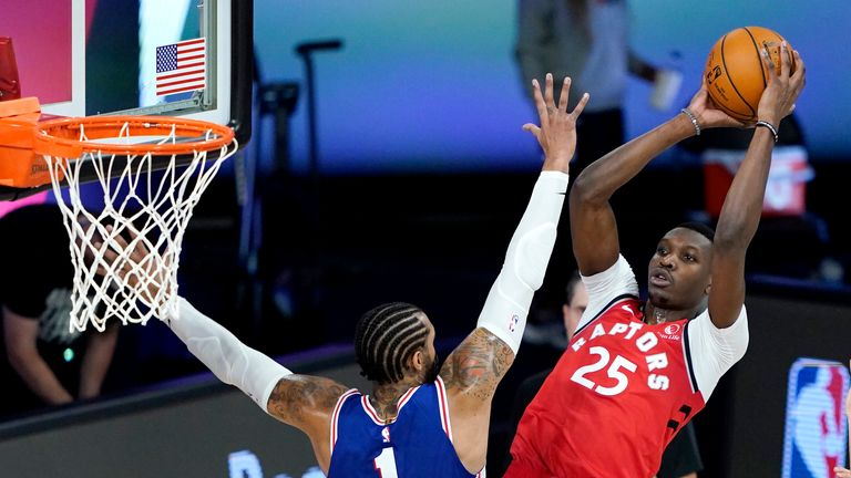 Chris Boucher #25 of the Toronto Raptors goes up for a shot against Mike Scott #1 of the Philadelphia 76ers during the second half at The Field House at ESPN Wide World Of Sports Complex on August 12, 2020 in Lake Buena Vista, Florida.