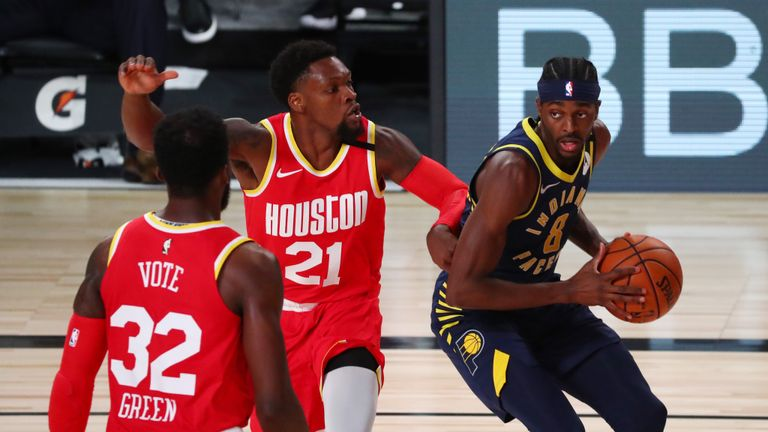 Justin Holiday #8 of the Indiana Pacers drives to the basket against Michael Frazier #21 and Jeff Green #32 of the Houston Rockets in the fourth quarter at AdventHealth Arena at ESPN Wide World Of Sports Complex on August 12, 2020 in Lake Buena Vista, Florida.