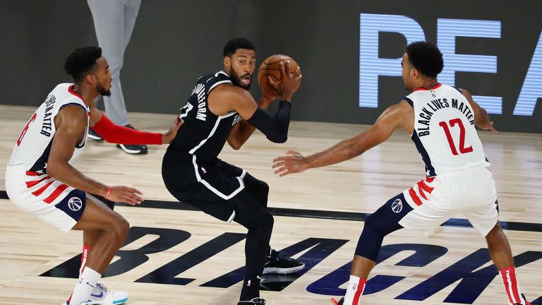 Brooklyn Nets guard Garrett Temple #17 holds the ball while defended by Washington Wizards forward Troy Brown Jr. #6 and guard Jerome Robinson #12 in the second half of a NBA basketball game at HP Field House at ESPN Wide World Of Sports Complex on August 2, 2020 in Lake Buena Vista, Florida.