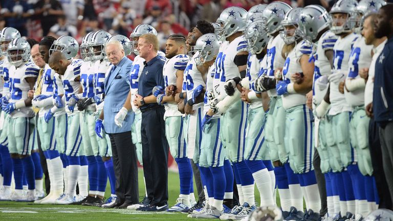 Dallas Cowboys players and owner Jerry Jones locked arms and briefly took a knee on the field before standing on the sideline throughout the playing of the national anthem against Arizona Cardinals in 2017