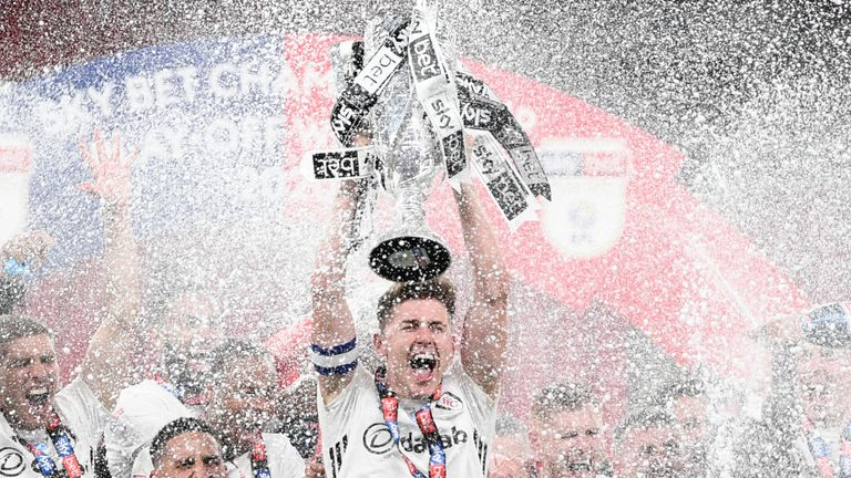 Tom Cairney celebrates promotion after the play-off final at Wembley