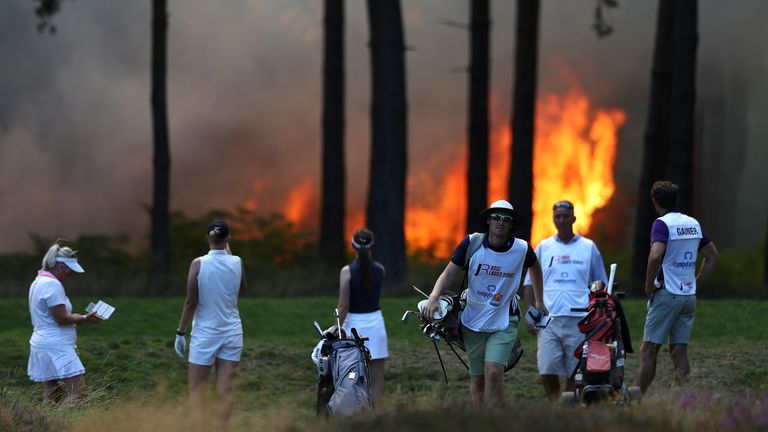 Players, Sophie Powell, Cara Gainer and Gabriella Cowley and their caddies look on after a fire behind the tenth hole stops play on day three of The Rose Ladies Series at Wentworth Golf Club
