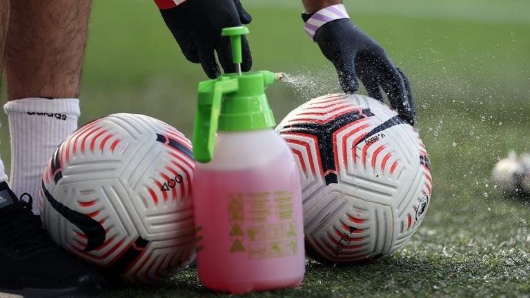 Staff spray match balls with disinfectant prior to kick-off
