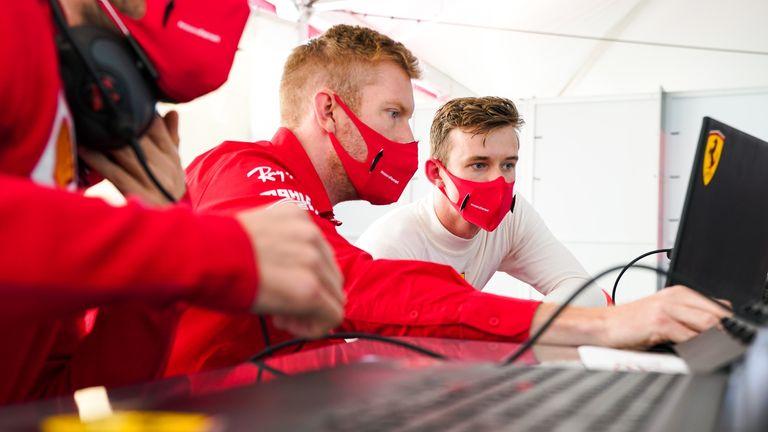 Callum Ilott (R) studies the data with Ferrari's engineers