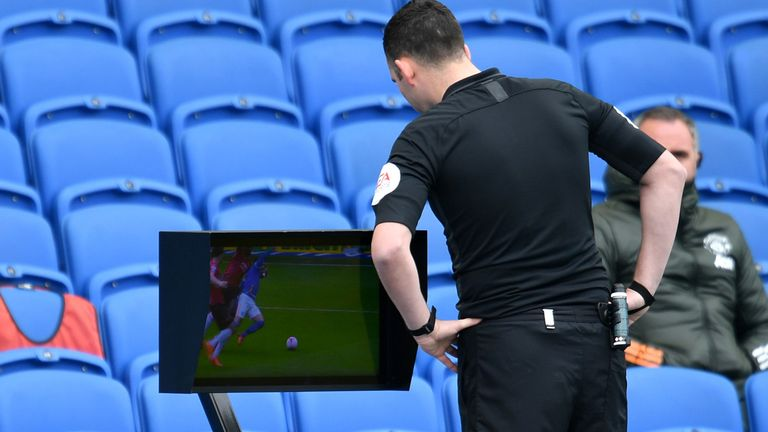 Referee Chris Kavanagh checks the pitchside monitor before deciding to not award Brighton a penalty