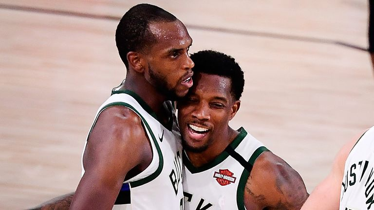 Eric Bledsoe hugs team-mate Khris Middleton after the Milwaukee Bucks' Game 4 overtime win over the Miami Heat