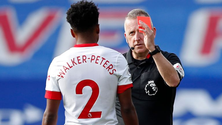 Referee Jonathan Moss shows a red card to Kyle Walker-Peters that is later overturned by VAR