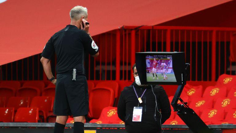 Martin Atkinson checks his monitor before awarding Palace the spot-kick