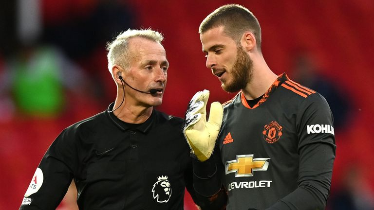 Referee Martin Atkinson speaks with with David De Gea after awarding a penalty to Crystal Palace