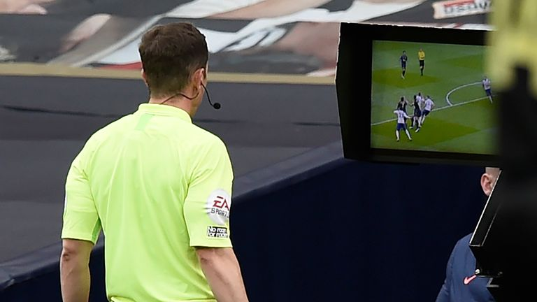 Referee Peter Bankes checks the pitchside monitor before awarding a penalty to Newcastle