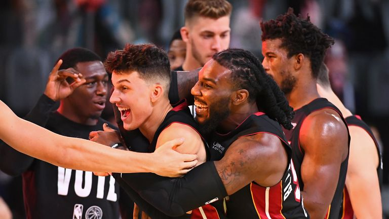 Jae Crowder and Tyler Herro of the Miami Heat smile and celebrate on the court after Game Four of the Eastern Conference Finals against the Boston Celtics