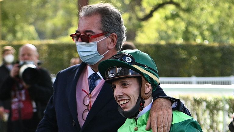 Italian jockey Cristian Demuro (R) is congratulated by French trainer Jean-Claude Rouget as they celebrate after victory on Sottsass in The Prix de l'Arc de Triomphe