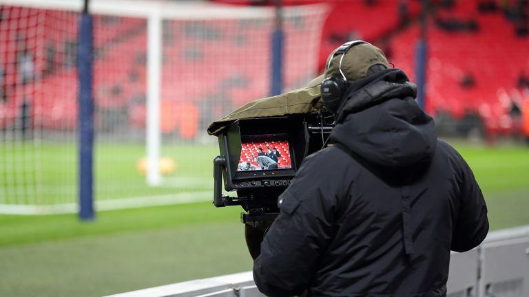 A TV camera operator filming a Premier League match