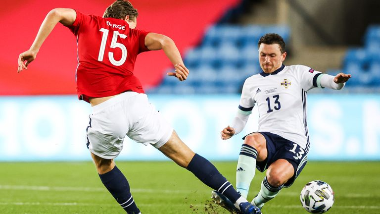 Corry Evans slides in to dispossess Sander Berge in the Nations League clash