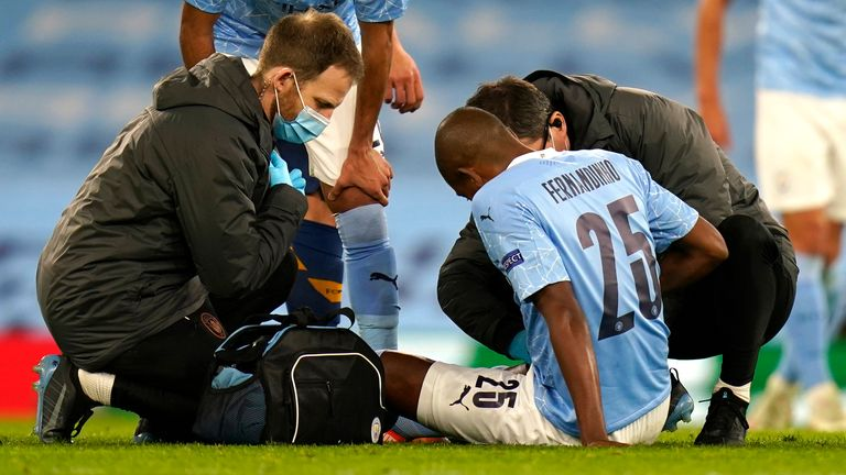 Fernandinho is treated by City's medical staff after going down injured in stoppage-time against Porto