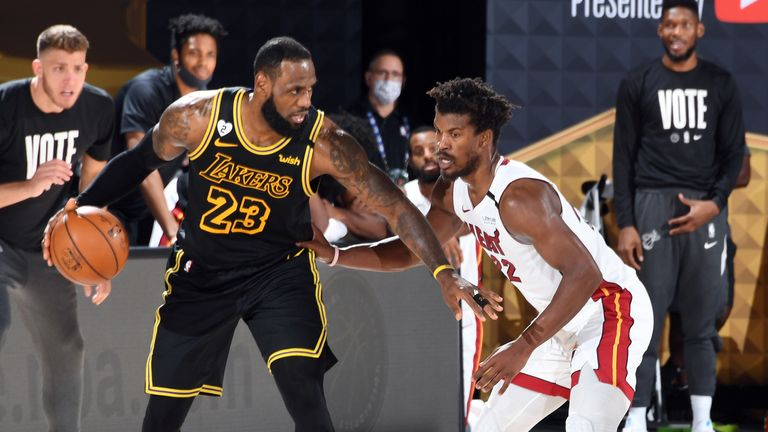 LeBron James of the Los Angeles Lakers handles the ball while Jimmy Butler of the Miami Heat plays defense during Game Five of the NBA Finals