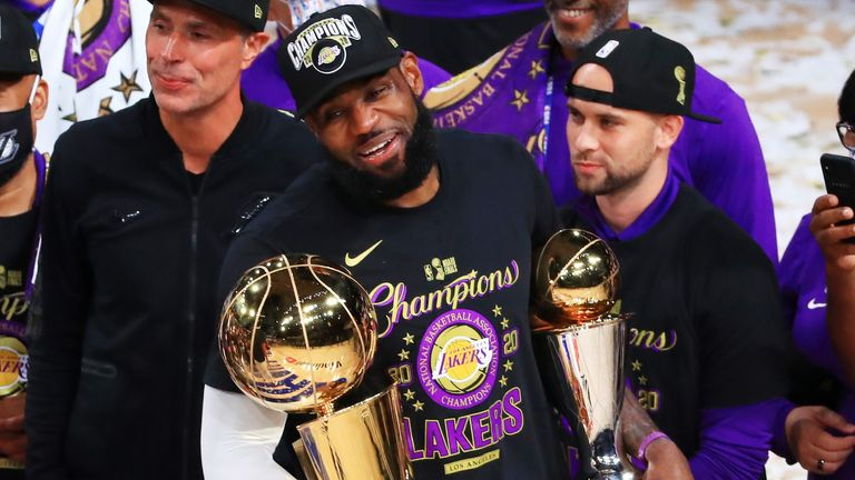 LeBron James holds the NBA championship and the Finals MVP trophies after the Lakers' Game 6 win