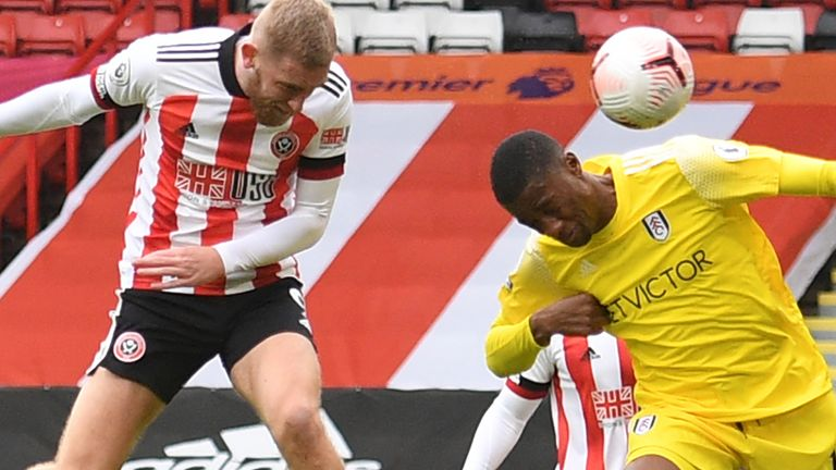 Sheffield United striker Oli McBurnie (L) has this header saved by Fulham's French goalkeeper Alphonse Areola (not pictured)