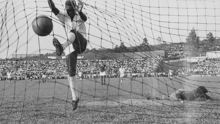 Brazilian footballer Pele in the net after scoring for Santos against Guarani of Paraguay, 1958.