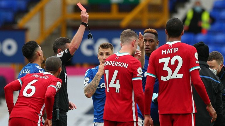 Richarlison (obscured) is shown a red card by referee Michael Oliver