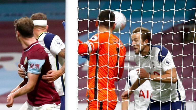Harry Kane of Tottenham Hotspur clears the ball from James Tarkowski of Burnley