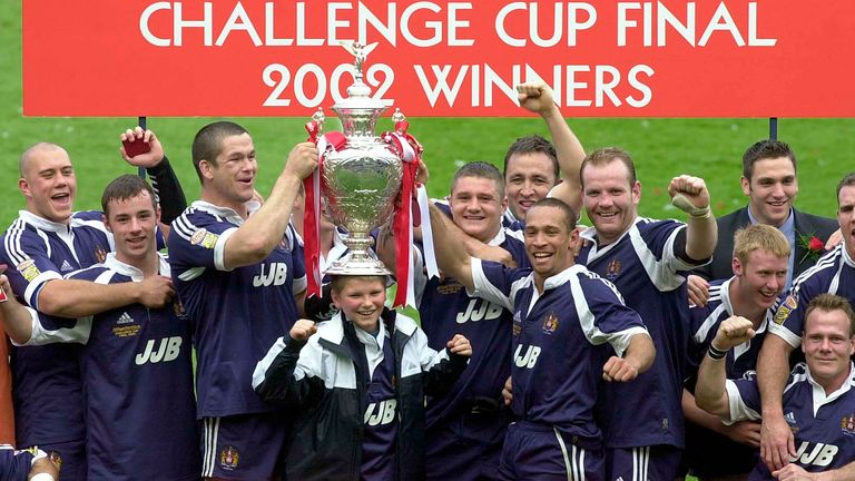 Adrian Lam and his Wigan team-mates lift the Challenge Cup after the 2002 final