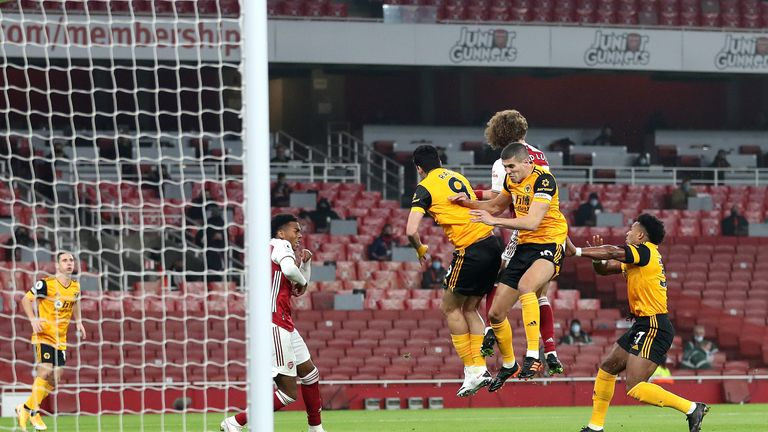 Conor Coady jumps for the ball immediately behind Jimenez and Luiz