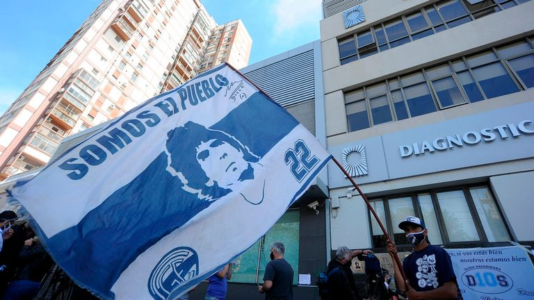 Supporters and well-wishers gather outside the private clinic where Diego Maradona underwent surgery