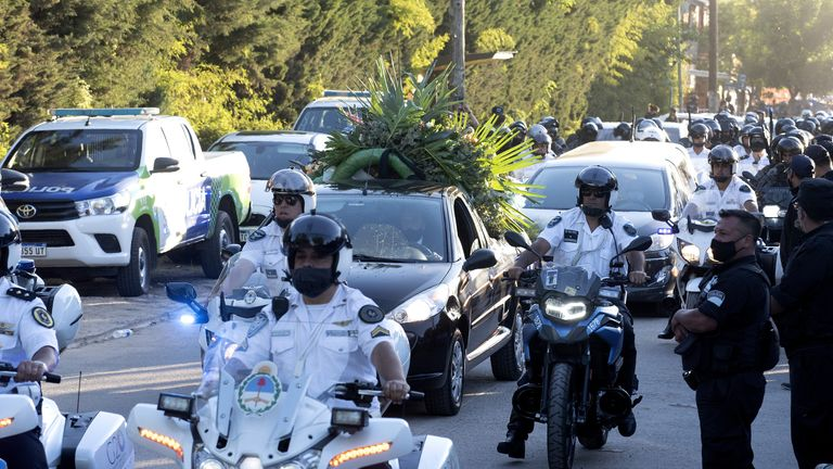 A flower car leads Diego Maradona's hearse into the cemetery ahead of his private burial