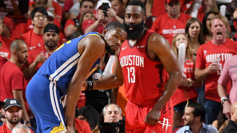 Kevin Durant of the Golden State Warriors and James Harden of the Houston Rockets look on during Game Three of the Western Conference Semifinals of the 2019 NBA Playoffs