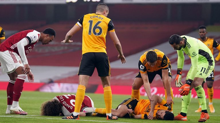 Players react after Arsenal's Brazilian defender David Luiz clashes heads with Wolverhampton Wanderers' Mexican striker Raul Jimenez during the English Premier League football match between Arsenal and Wolverhampton Wanderers at the Emirates Stadium in London on November 29, 2020