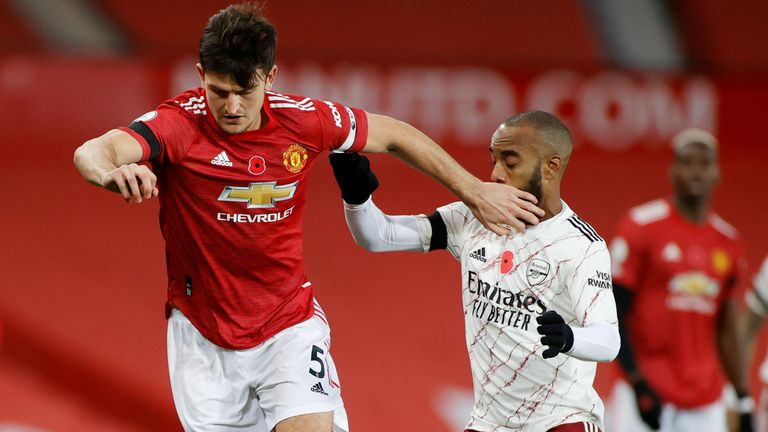Harry Maguire competes for possession with Alexandre Lacazette