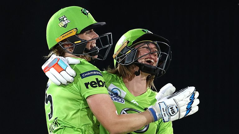 Heather Knight (left) celebrates Sydney Thunder's Women's Big Bash League win with captain Rachael Haynes