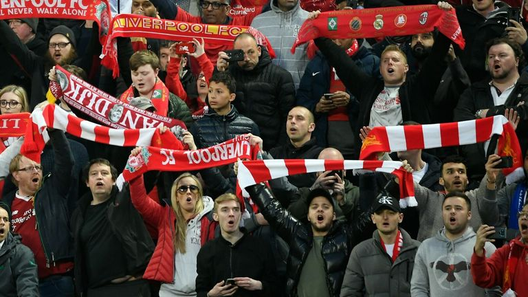 Liverpool fans at Anfield hold their scarves aloft