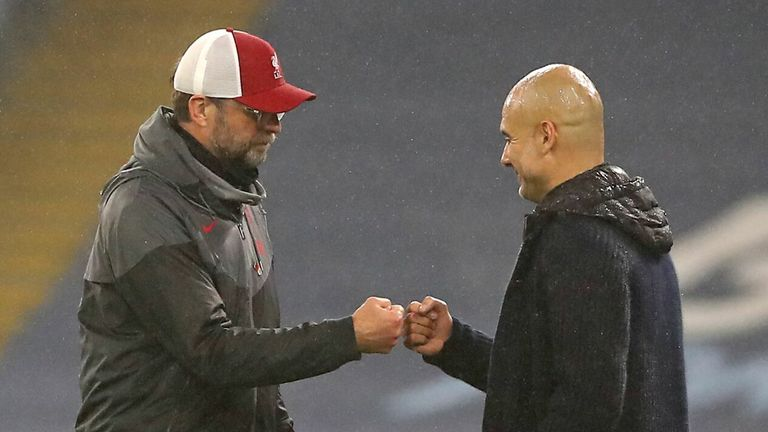 Jurgen Klopp (L) bumps fists with Manchester City's Spanish manager Pep Guardiola (C) at the end of the game during the English Premier League football match between Manchester City and Liverpool at the Etihad Stadium in Manchester, north west England, on November 8, 2020. - The game ended 1-1